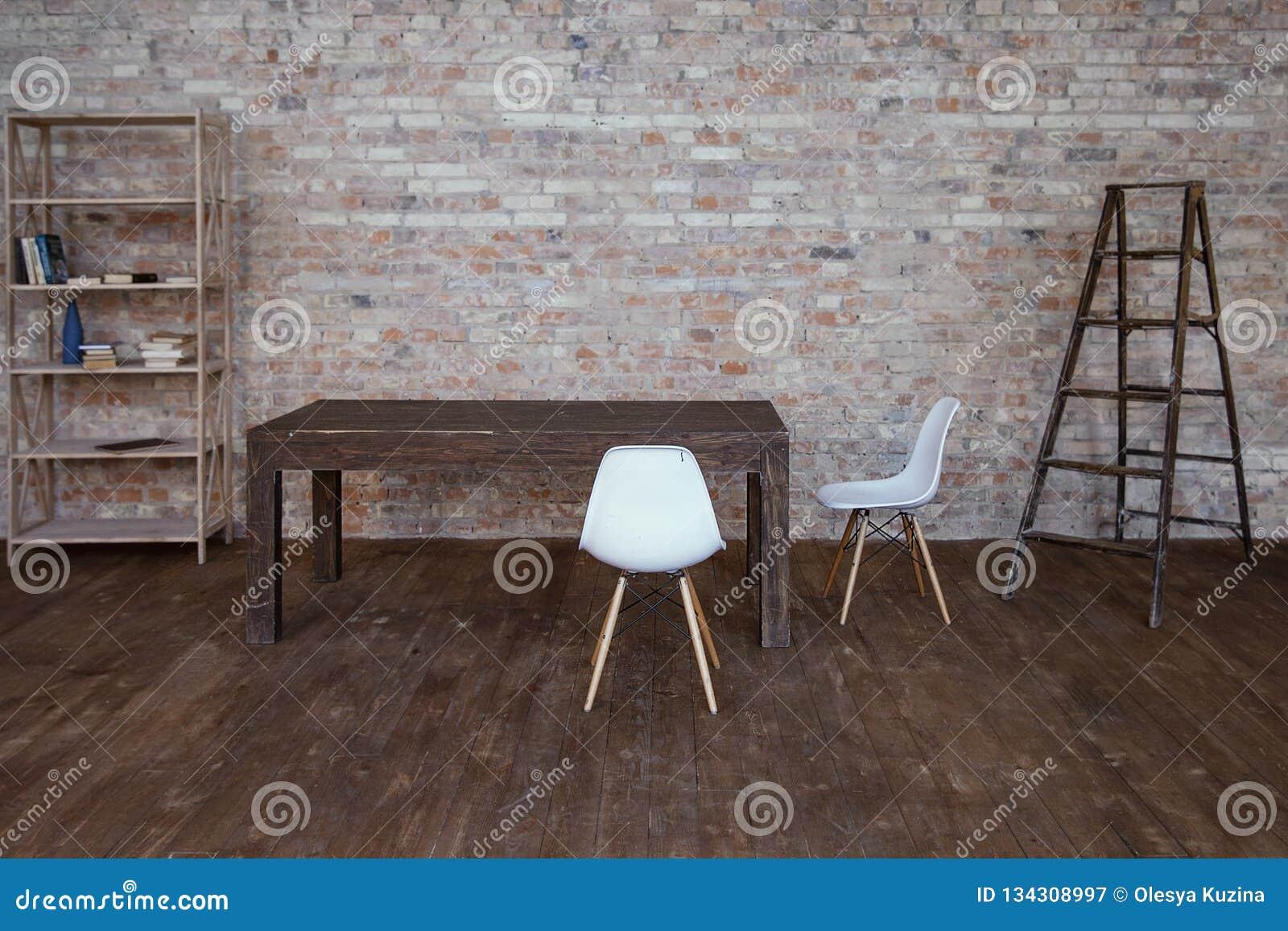 Conceptuele lege witte houten voetstoelen met bakstenen muur en grijze houten vloer