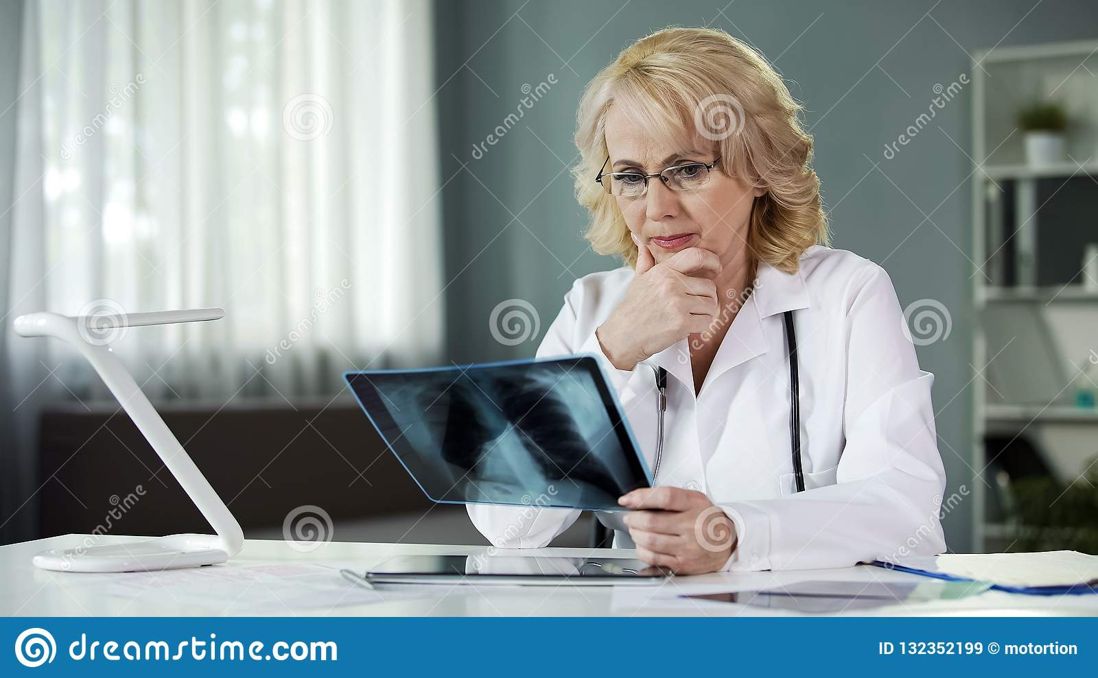 Concerned female pulmonologist examining X-ray of patient s lungs, diagnostics