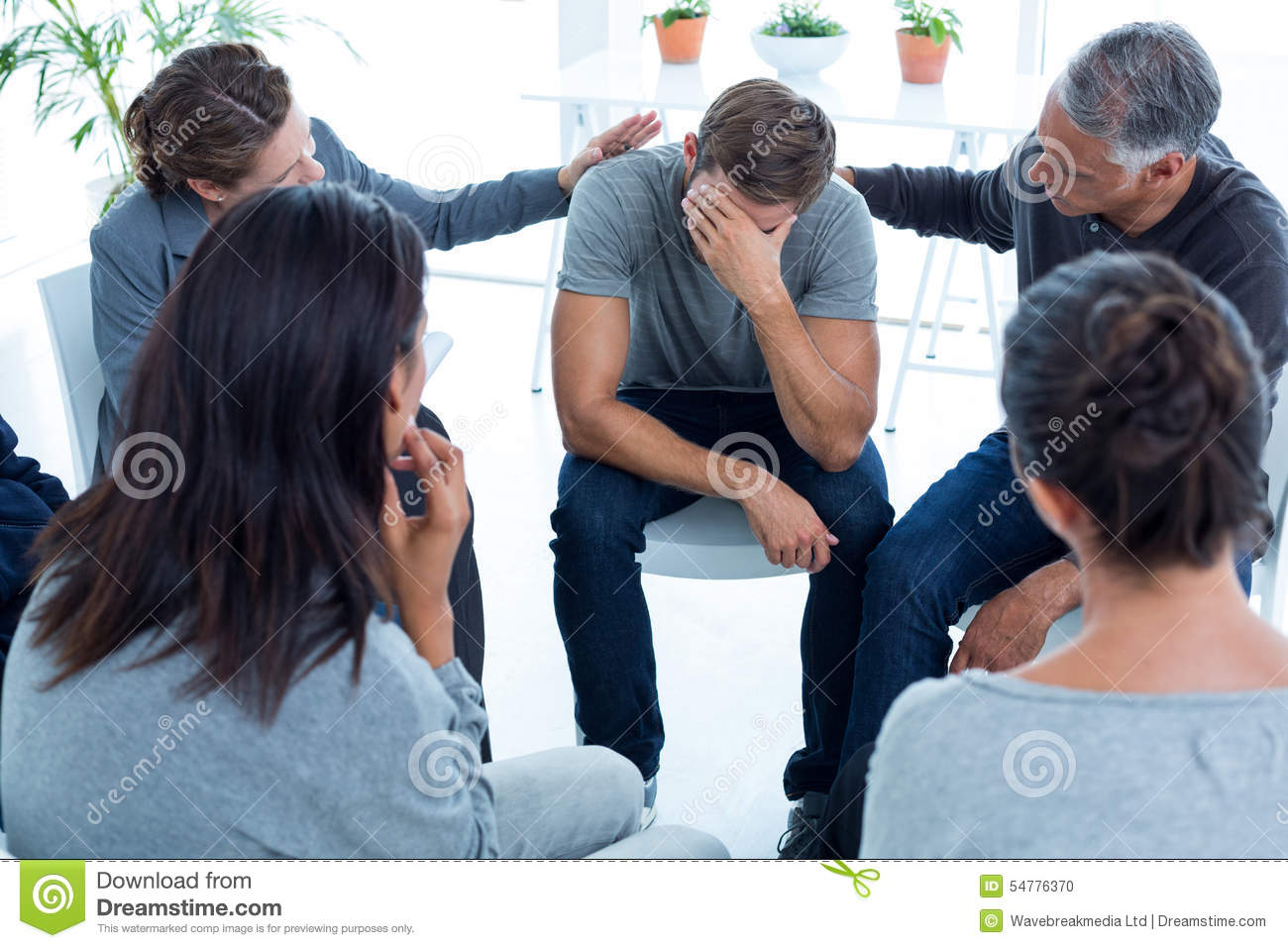 Concerned patients comforting another in rehab group