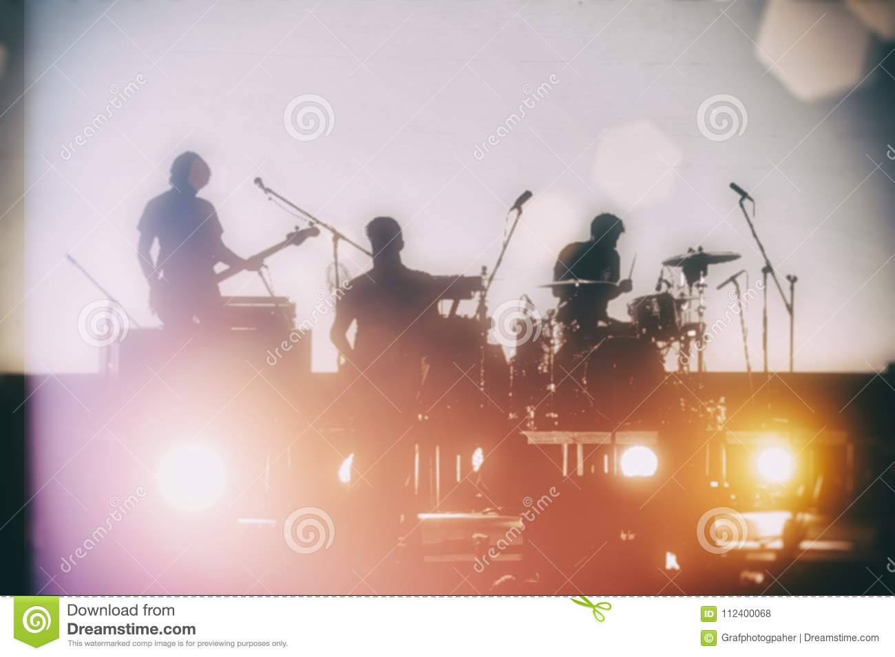 Concert of a musical rock band. Silhouettes of musicians on a se