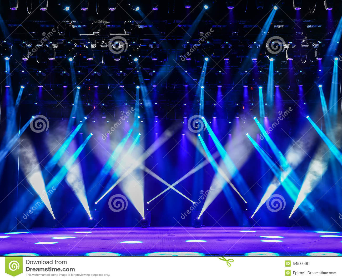 Illuminated empty theater stage with fog and blue rays of light.