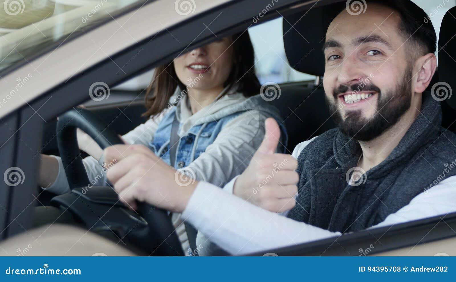 Concessionário automóvel de visita A família bonita é de fala e de sorriso ao sentar-se em seu carro novo o homem novo mostra o d