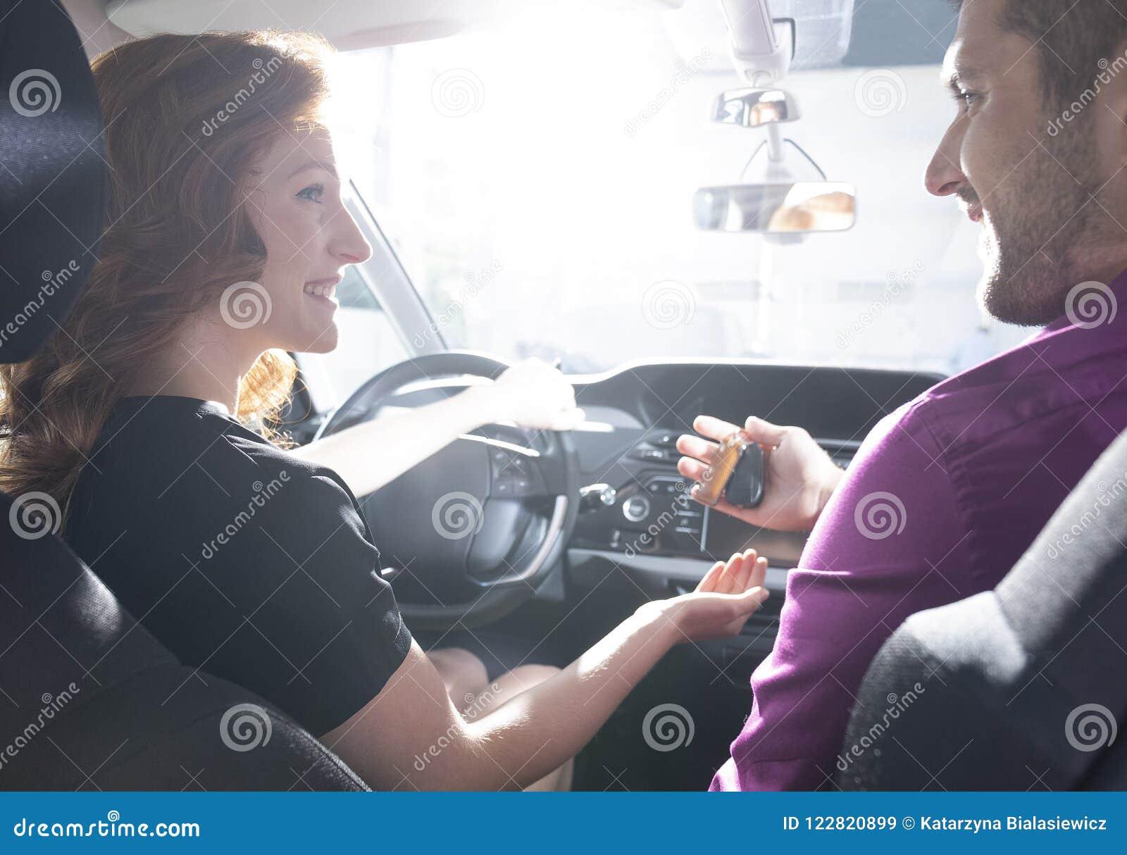 Concessionário automóvel feliz que dá chaves à mulher de sorriso durante a movimentação do teste