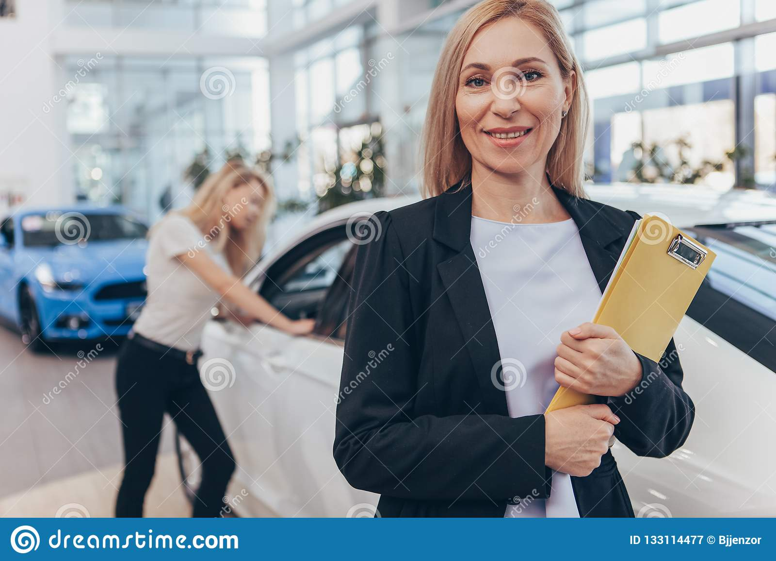 Concessionário automóvel profissional que ajuda seu cliente fêmea