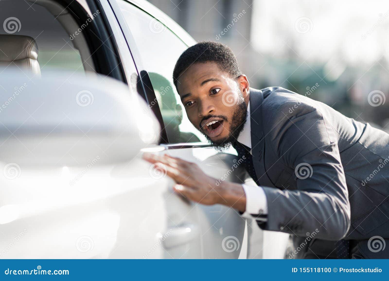 Concession?rio autom?vel de visita Homem do Afro que abraça seu carro novo