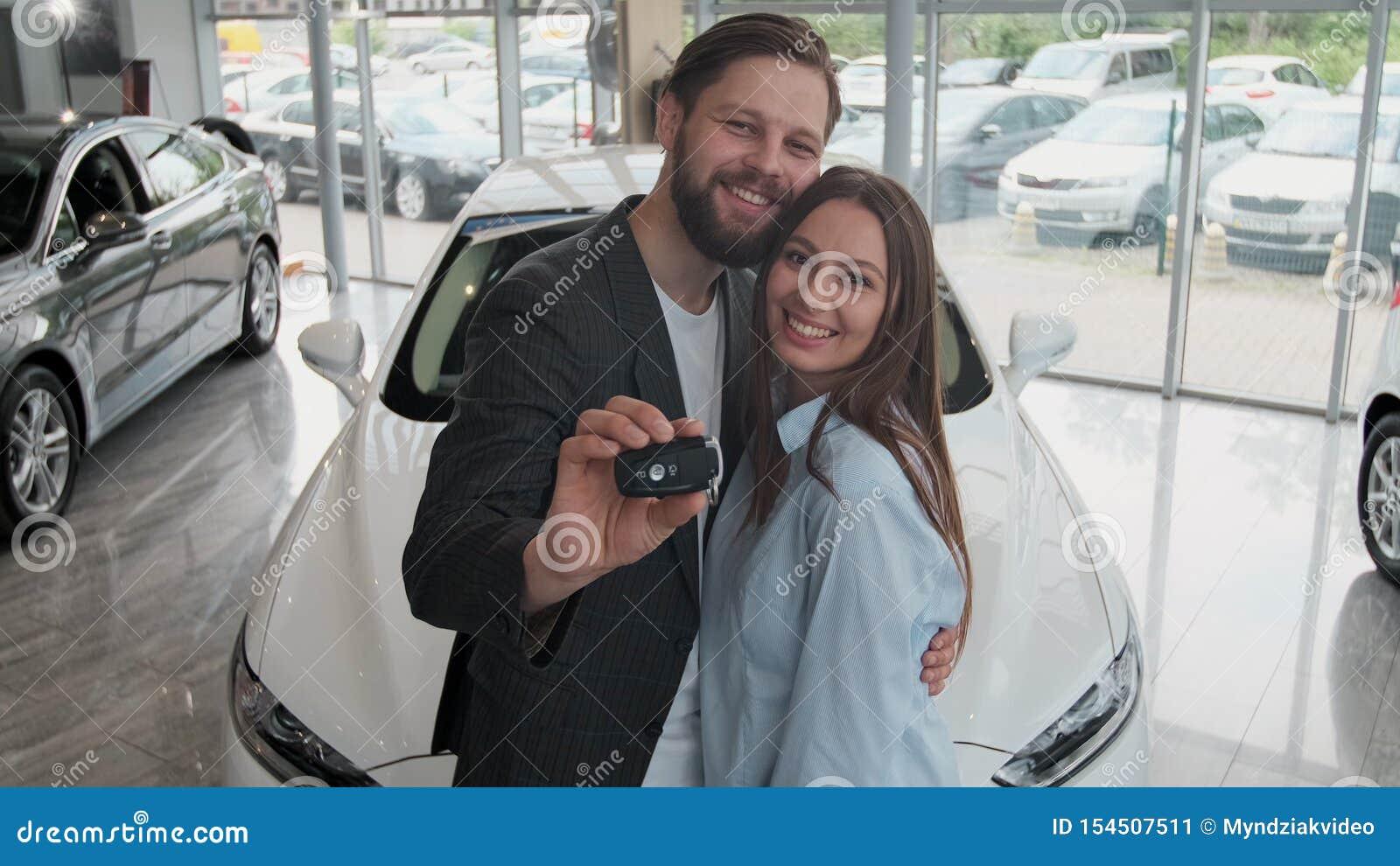 Concession?rio autom?vel de visita O par bonito est? guardando uma chave de seu carro novo, olhando a c?mera e o sorriso