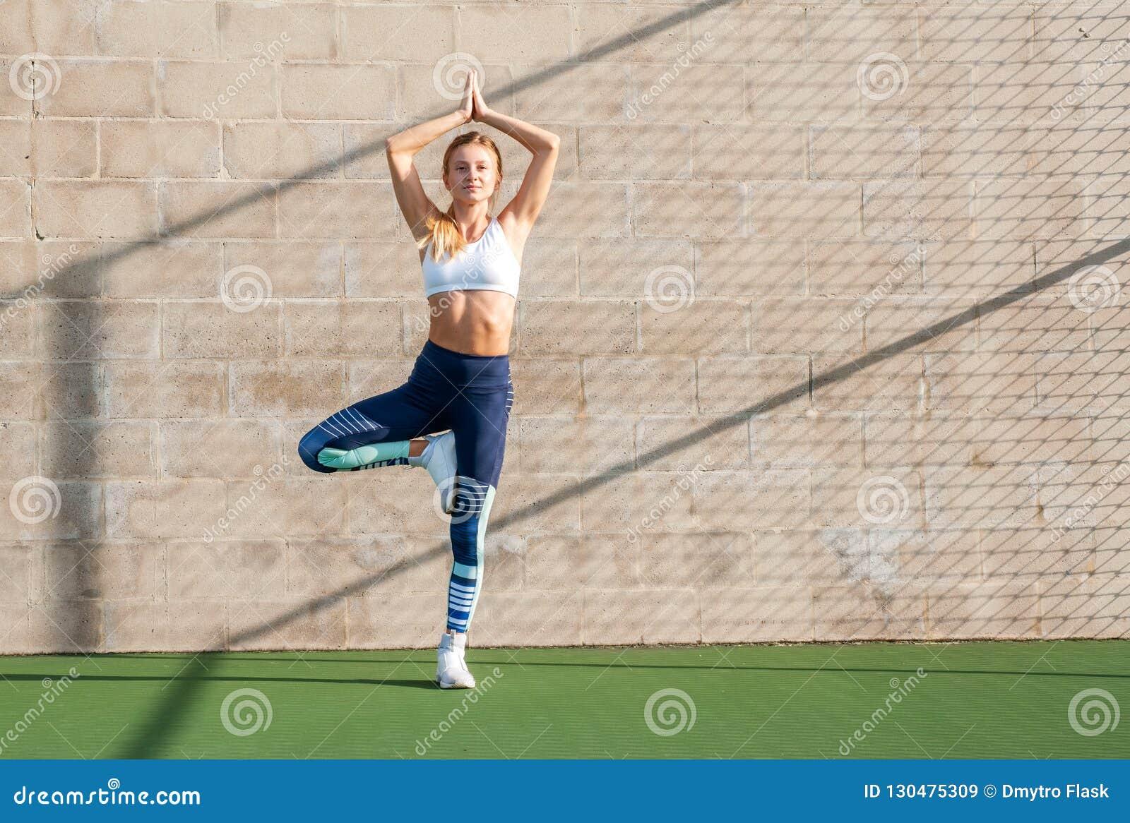 Concetti di yoga La donna di forma fisica in abiti sportivi sta facendo l esercizio sopra