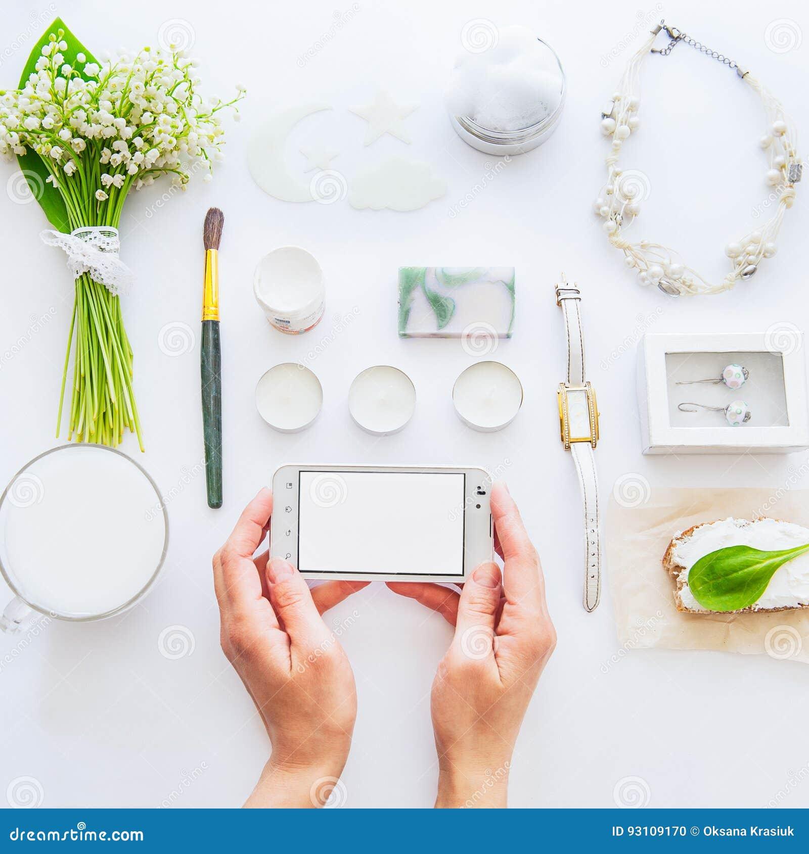 Concetto del blog di bellezza La fine sulle mani femminili tiene lo smartphone sui precedenti dei datails e degli accessori bianc
