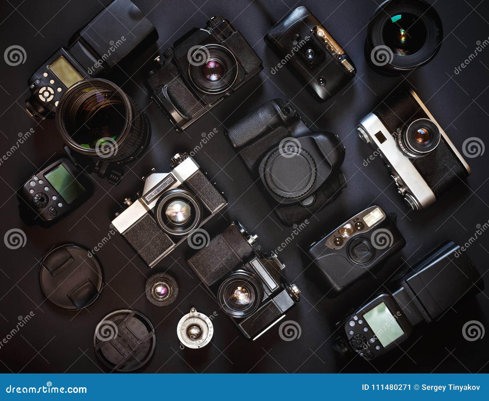 Concetto del posto di lavoro della fotografia Film d annata e macchine fotografiche digitali della raccolta, su fondo nero, vista
