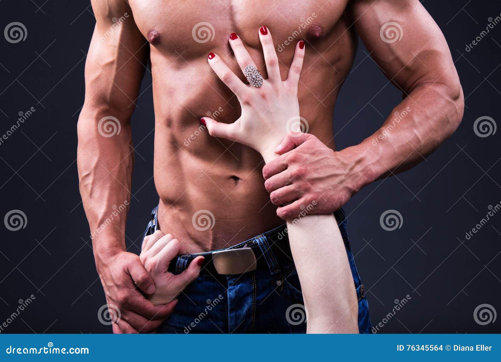 Concetto del sesso - vicino su del maschio muscolare commovente BO delle mani femminili