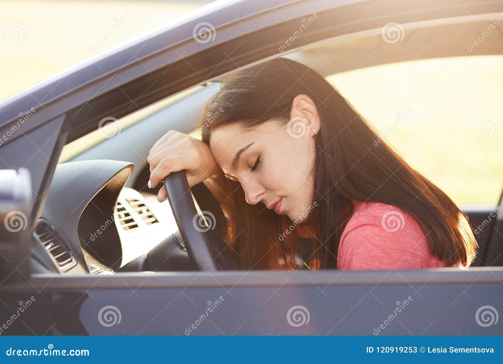 Concetto del trasporto Il bello driver stanco della donna ha espressione sonnolenta, fermata sulla strada come potrà l azionament