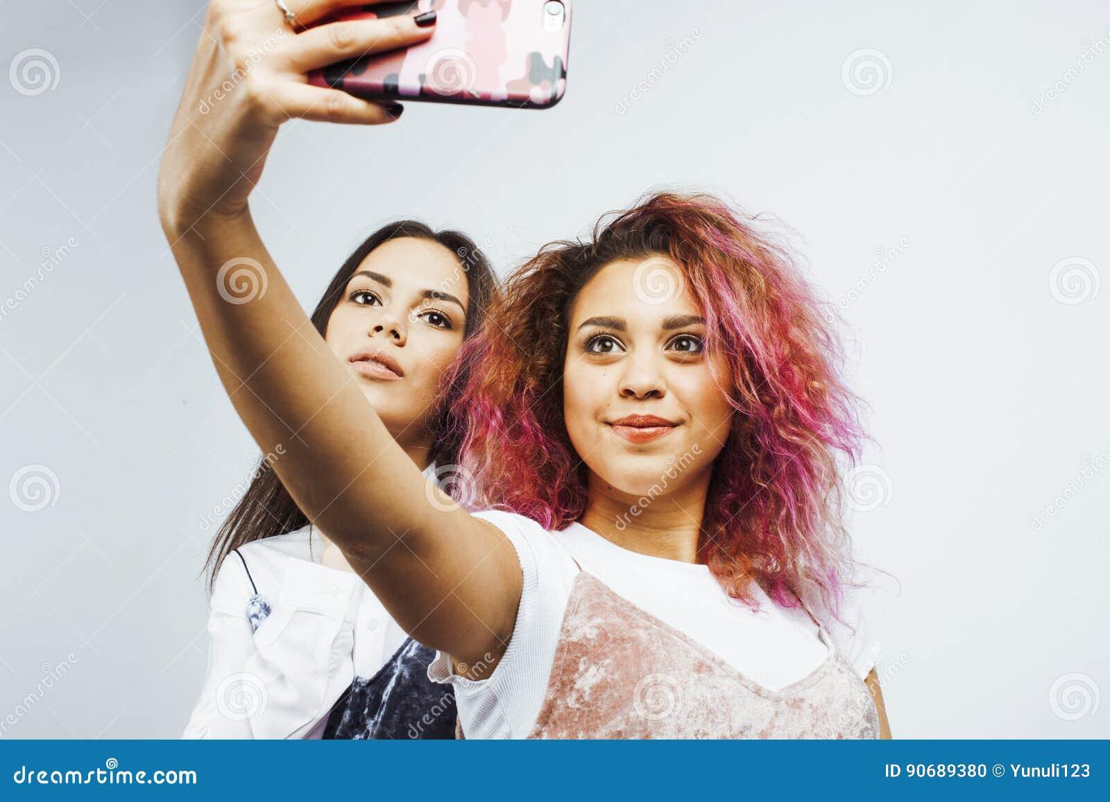 Concetto della gente di stile di vita: ragazza teenager dei pantaloni a vita bassa moderni abbastanza alla moda due divertendosi