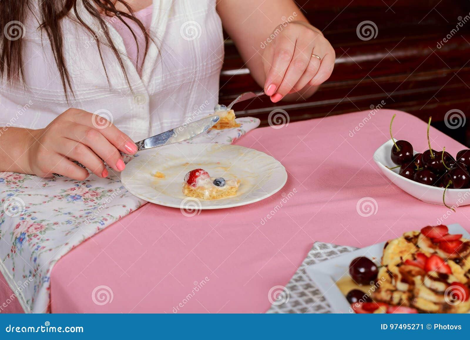 Concetto della gente e del dessert - vicino su della donna che mangia cialda con la fragola