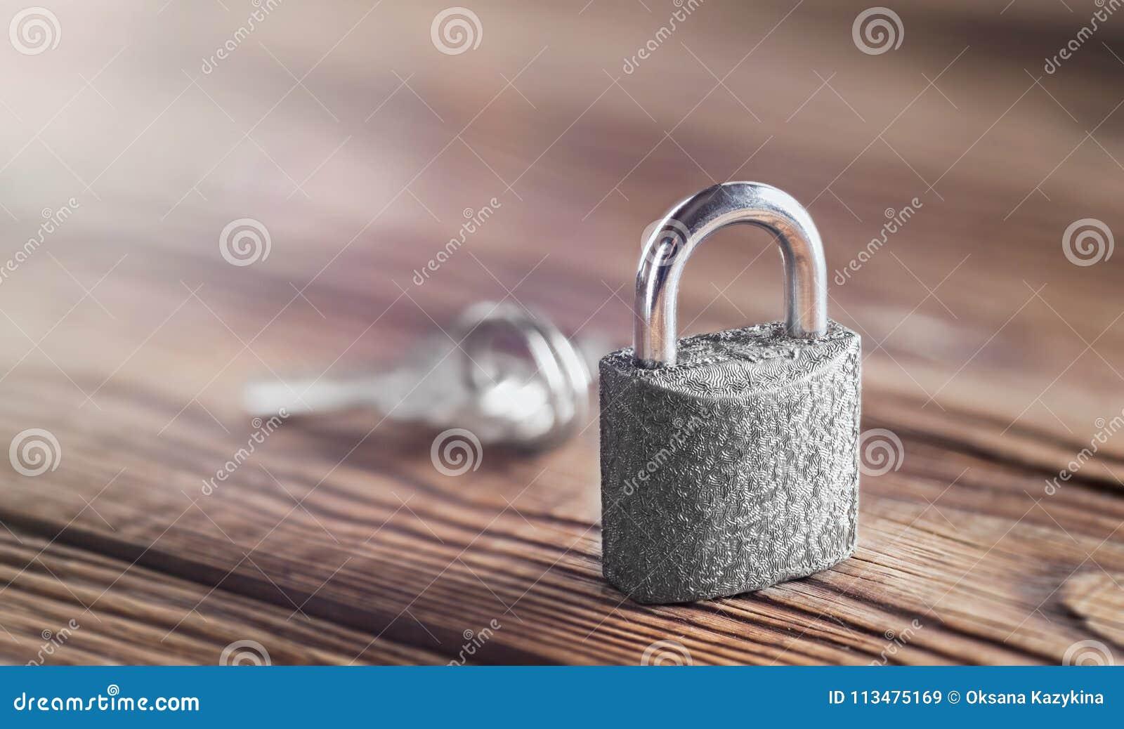 Concetto della proprietà con il simbolo di sicurezza, lucchetto della serratura con la chiave su fondo di legno