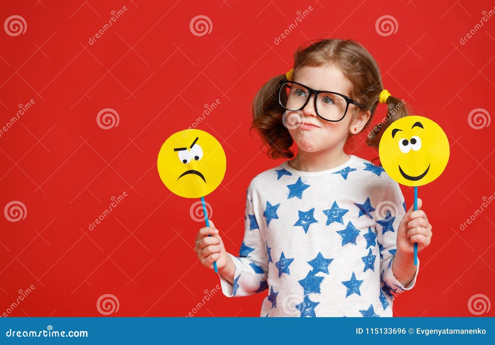 Concetto delle emozioni del ` s dei bambini la ragazza del bambino sceglie fra un triste