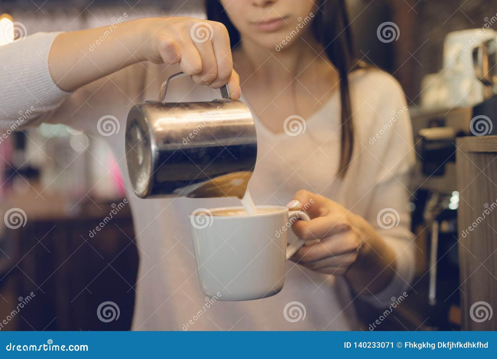 Concetto di affari del caffè - barista di signora del primo piano in latte preparante e di versamento del grembiule