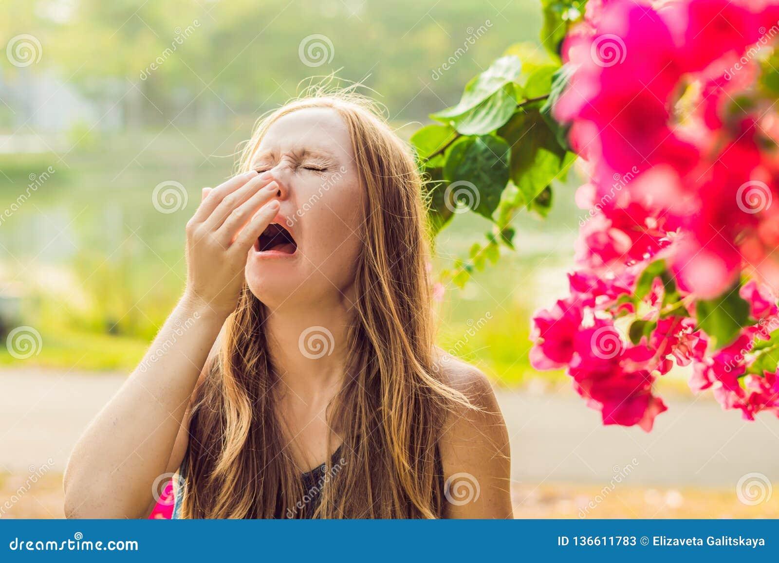 Concetto di allergia del polline La giovane donna sta andando starnutire Alberi di fioritura nel fondo