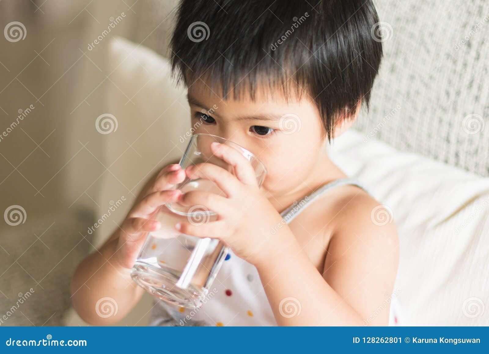 Concetto di bellezza e di salute - tenuta e drinki asiatici della bambina