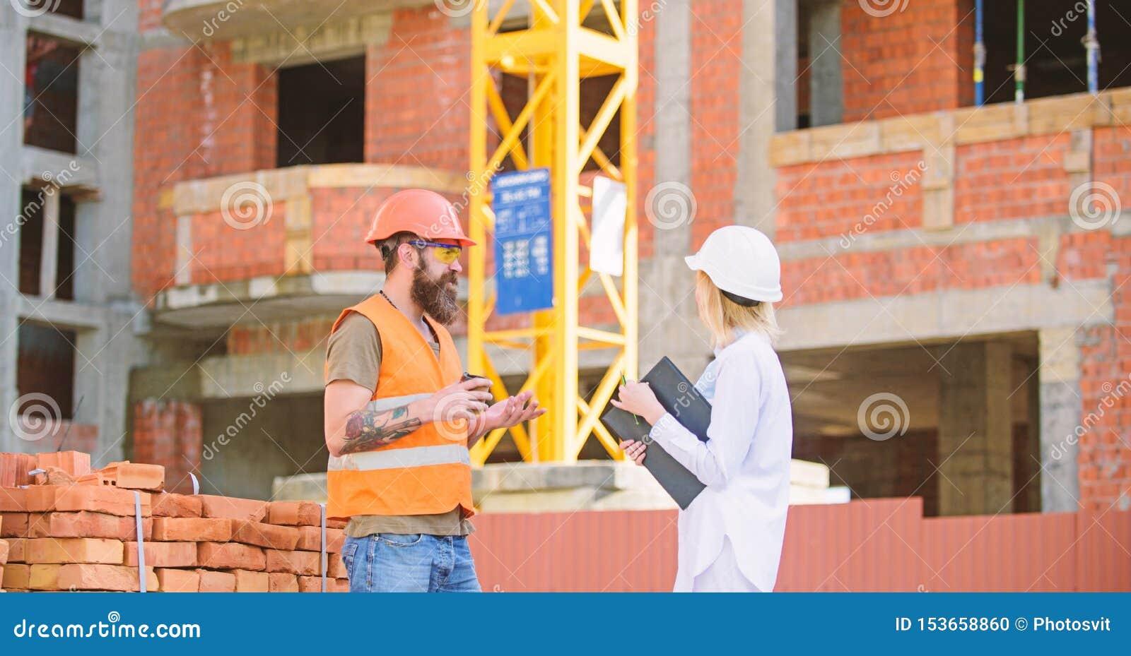 Concetto di comunicazione del gruppo della costruzione L ingegnere della donna ed il costruttore brutale comunicano il fondo del