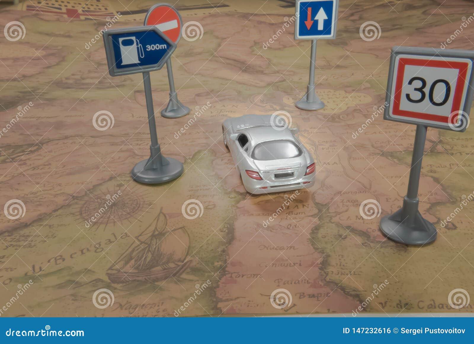 Concetto di corsa Automobile del giocattolo sulla mappa di mondo d annata con il segnale stradale