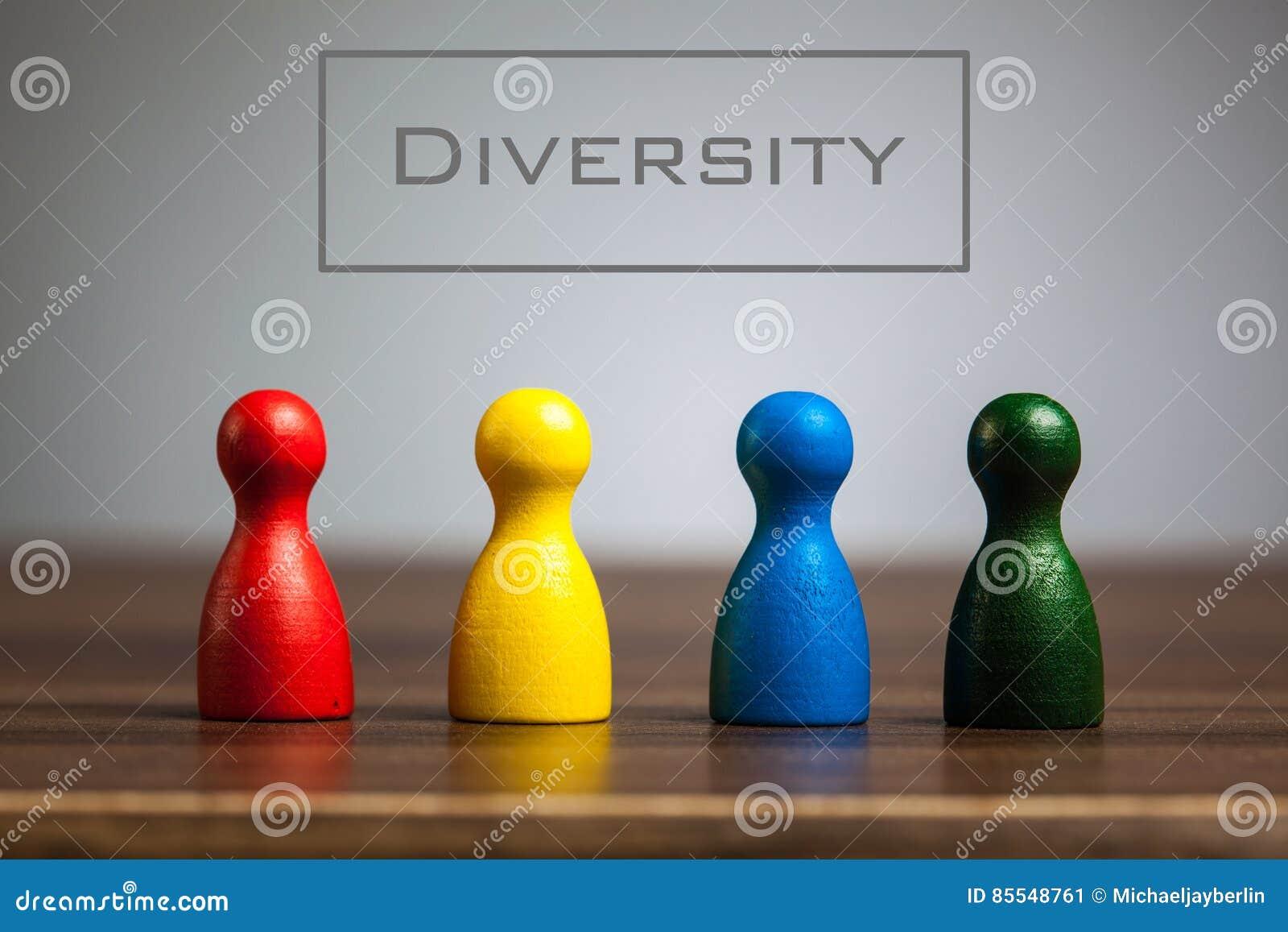 Concetto di diversità con quattro figurine del pegno sulla tavola