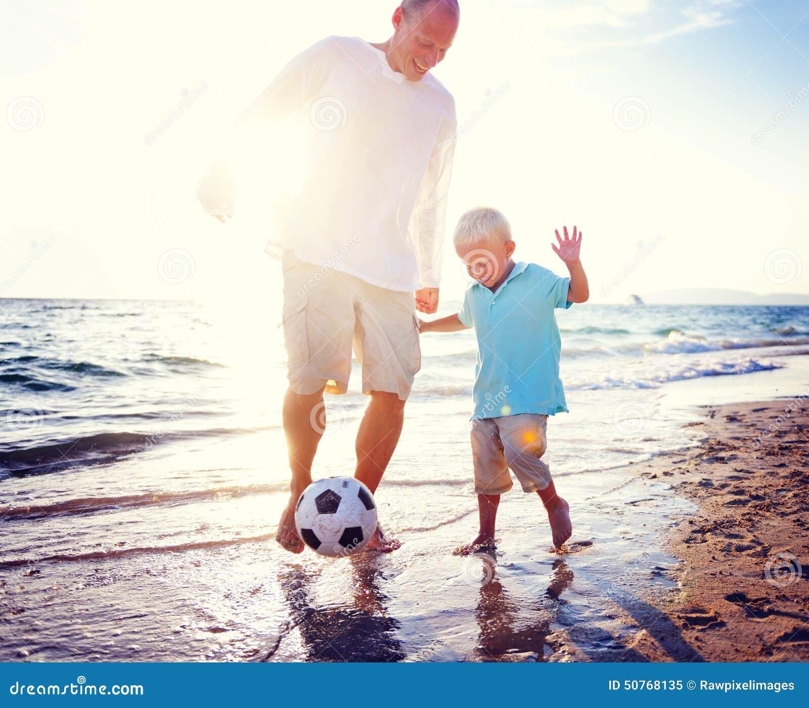 Concetto di estate della spiaggia di Son Playing Soccer del padre