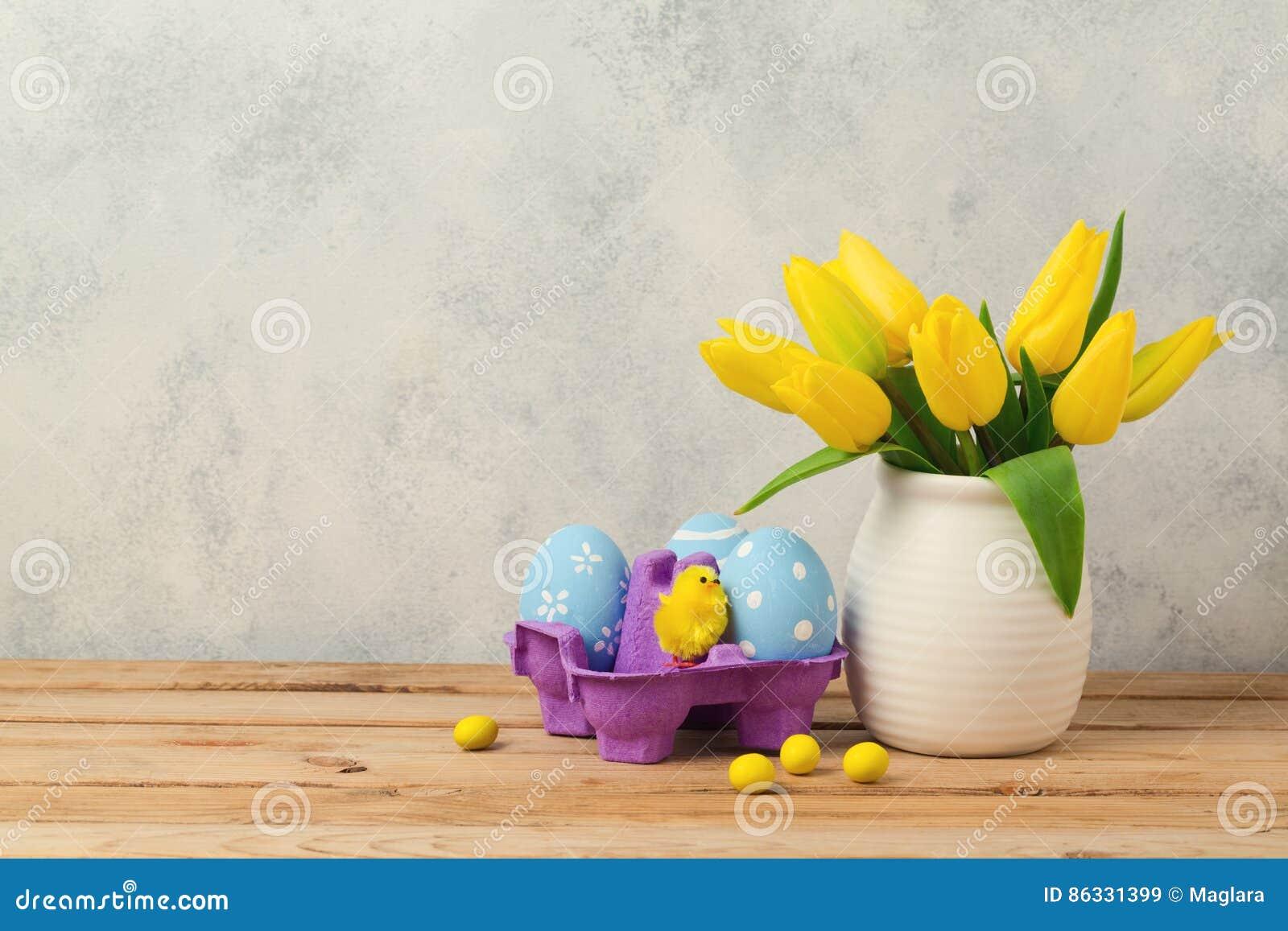 Concetto di festa di Pasqua con i fiori e le uova del tulipano sulla tavola di legno