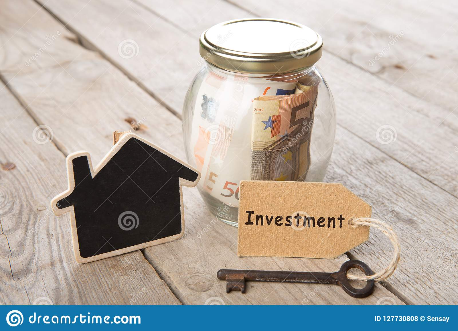 Concetto di finanza del bene immobile - vetro dei soldi con la parola di investimento