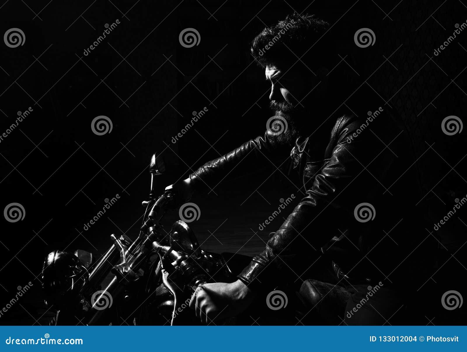 Concetto di mascolinità Uomo con la barba, motociclista in bomber che si siede sulla bici del motore nell oscurità, fondo nero ma