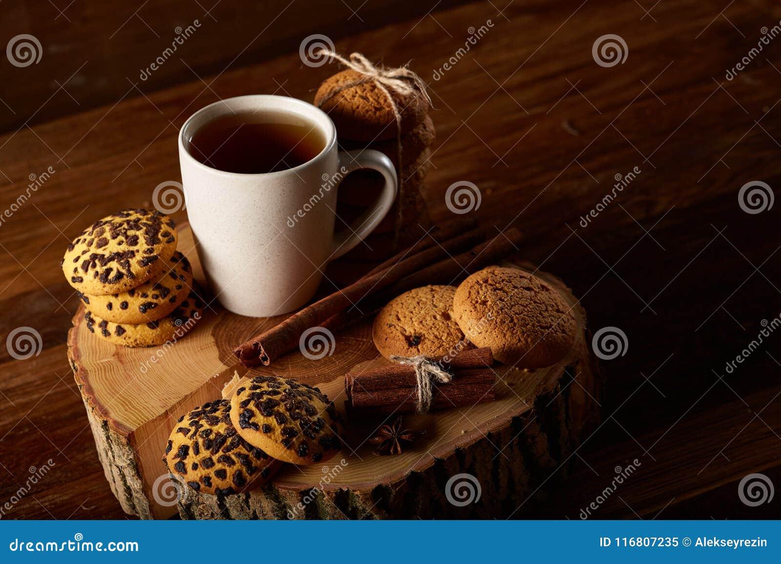 Concetto di Natale con una tazza di tè, dei biscotti e delle decorazioni caldi su un ceppo sopra fondo di legno, fuoco selettivo