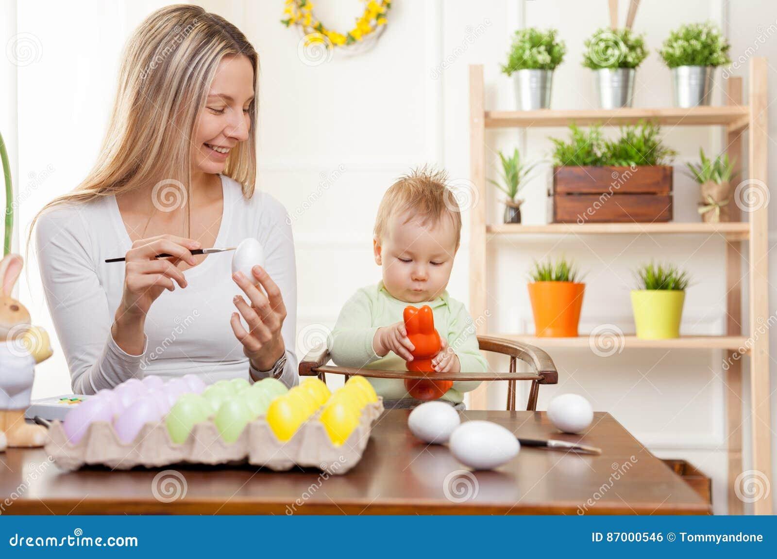 Concetto di Pasqua Madre felice e suo il bambino sveglio che si preparano per Pasqua