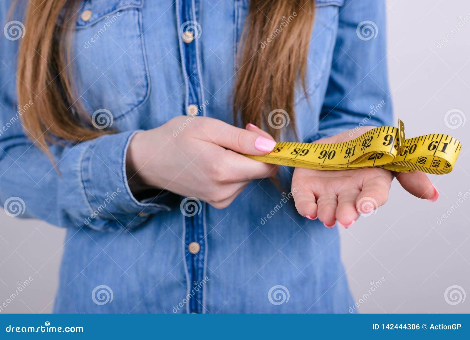 Concetto di problema di 90 60 90 norme Foto potata del primo piano di signora rigorosa che tiene giallo sottile con il metro di c