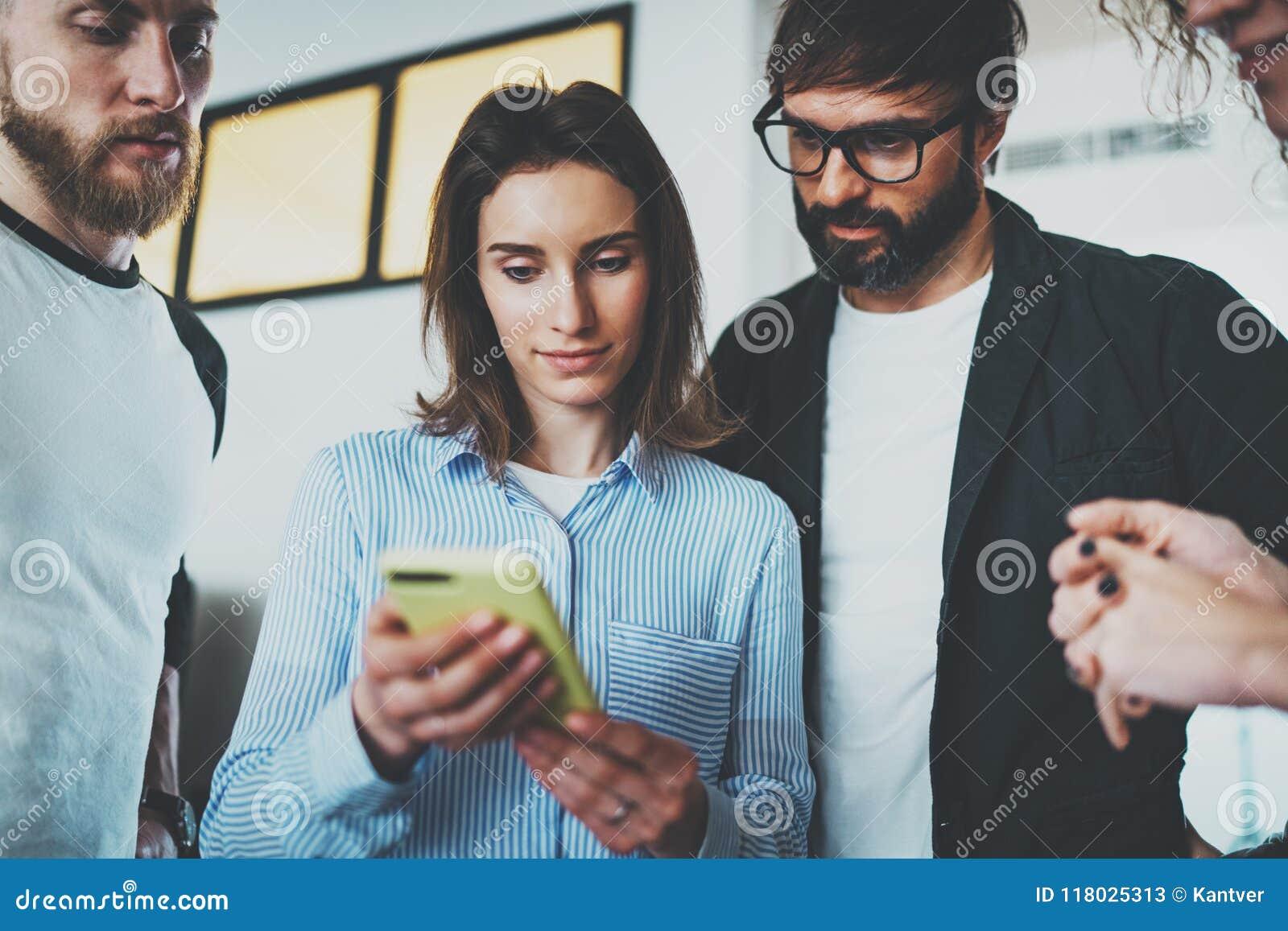 Concetto di riunione d affari dei colleghe Giovani donne che tengono la mano mobile dello smartphone e che mostrano informazioni