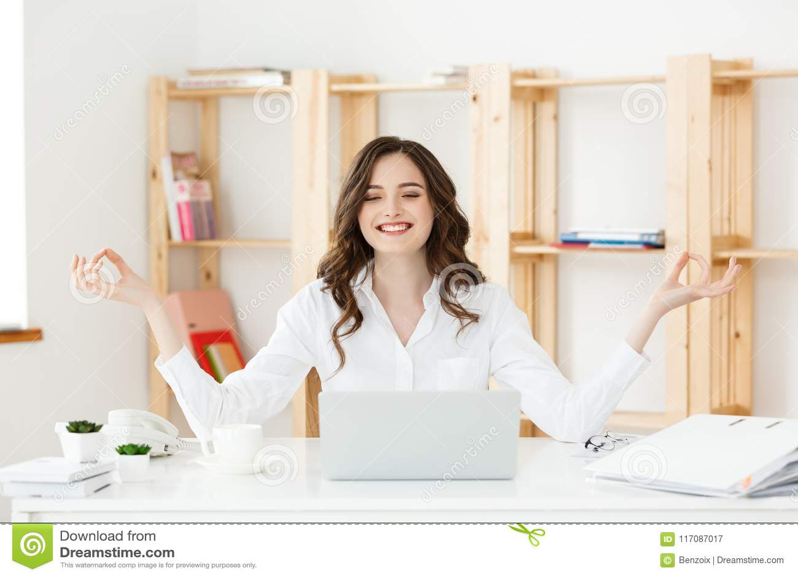 Concetto di salute e di affari: Giovane donna vicino al computer portatile, meditazione di pratica del ritratto alla scrivania, d