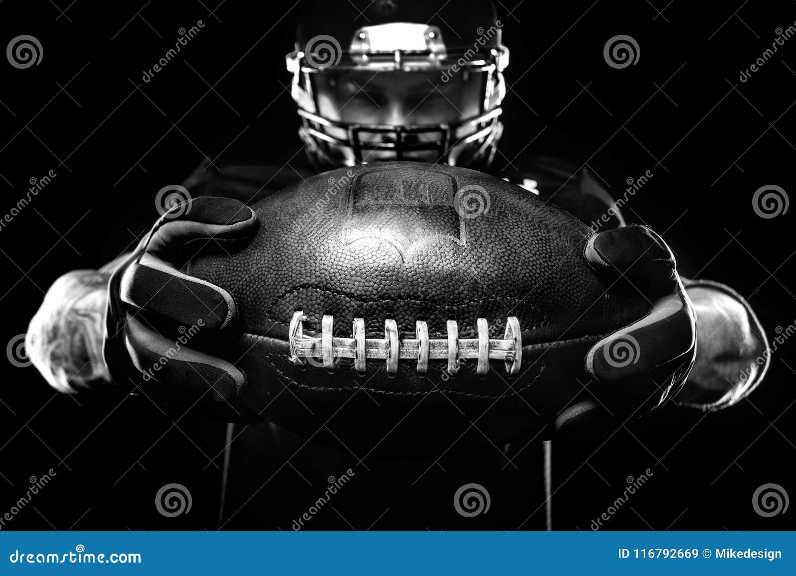Concetto di sport Giocatore dello sportivo di football americano su fondo nero Concetto di sport