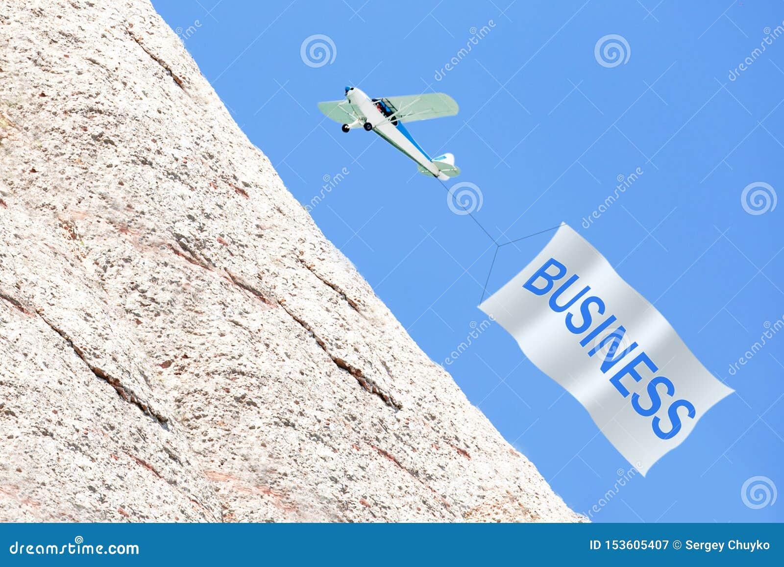 Concetto di sviluppo di affari Aeroplano che tira insegna con l AFFARE in cielo