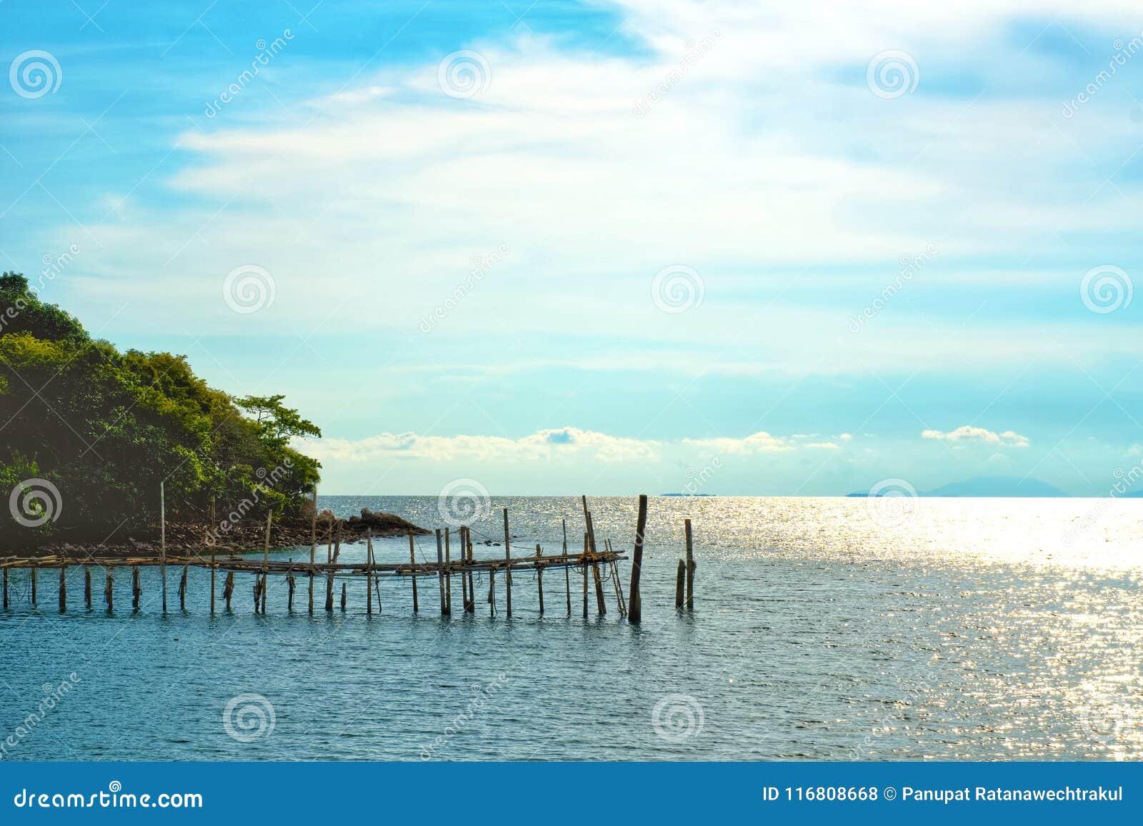 Concetto di tempo di vacanza, tempo della spiaggia sulla terra di legno con la vista del mare