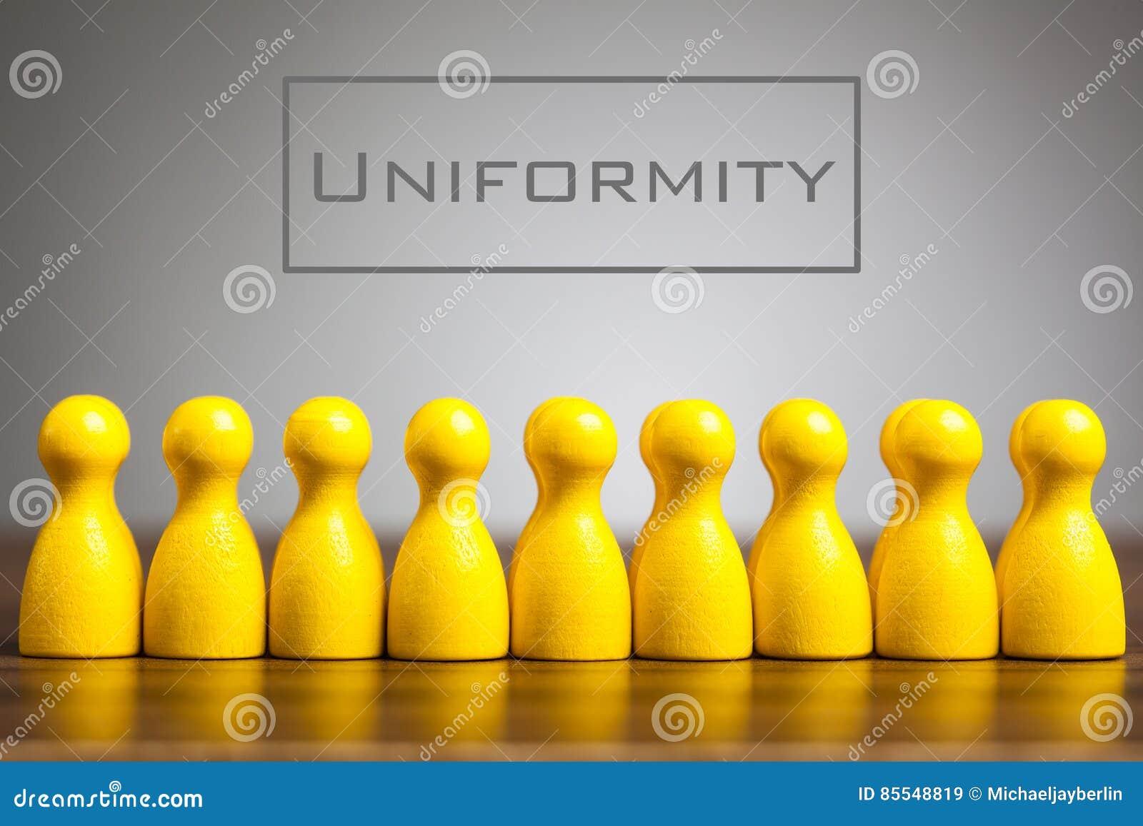 Concetto di uniformità con le figurine del pegno sulla tavola,