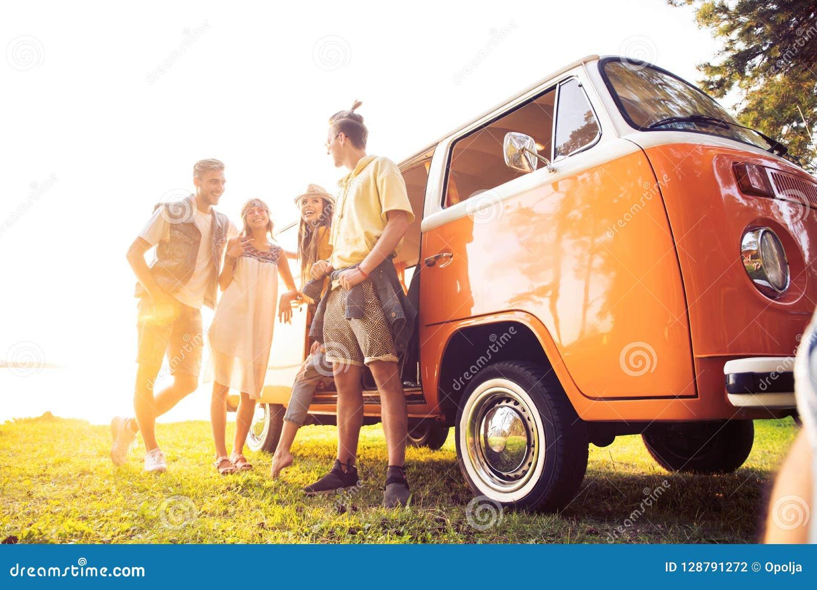 Concetto di vacanze estive, di viaggio stradale, di vacanza, di viaggio e della gente - giovani amici sorridenti di hippy diverte