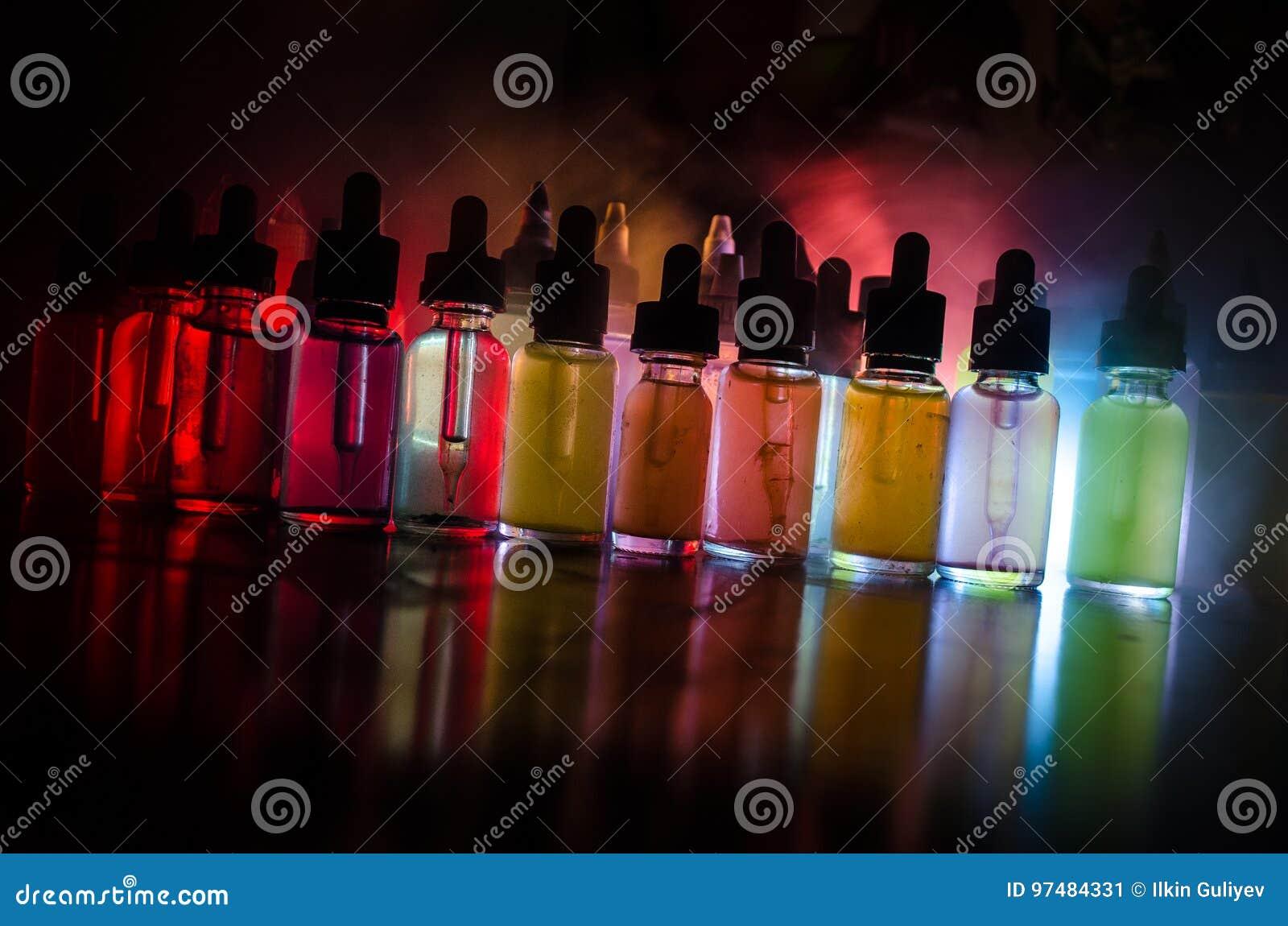 Concetto di Vape Nuvole di fumo e bottiglie liquide del vape su fondo scuro Effetti della luce Utile come pubblicità o del vape o