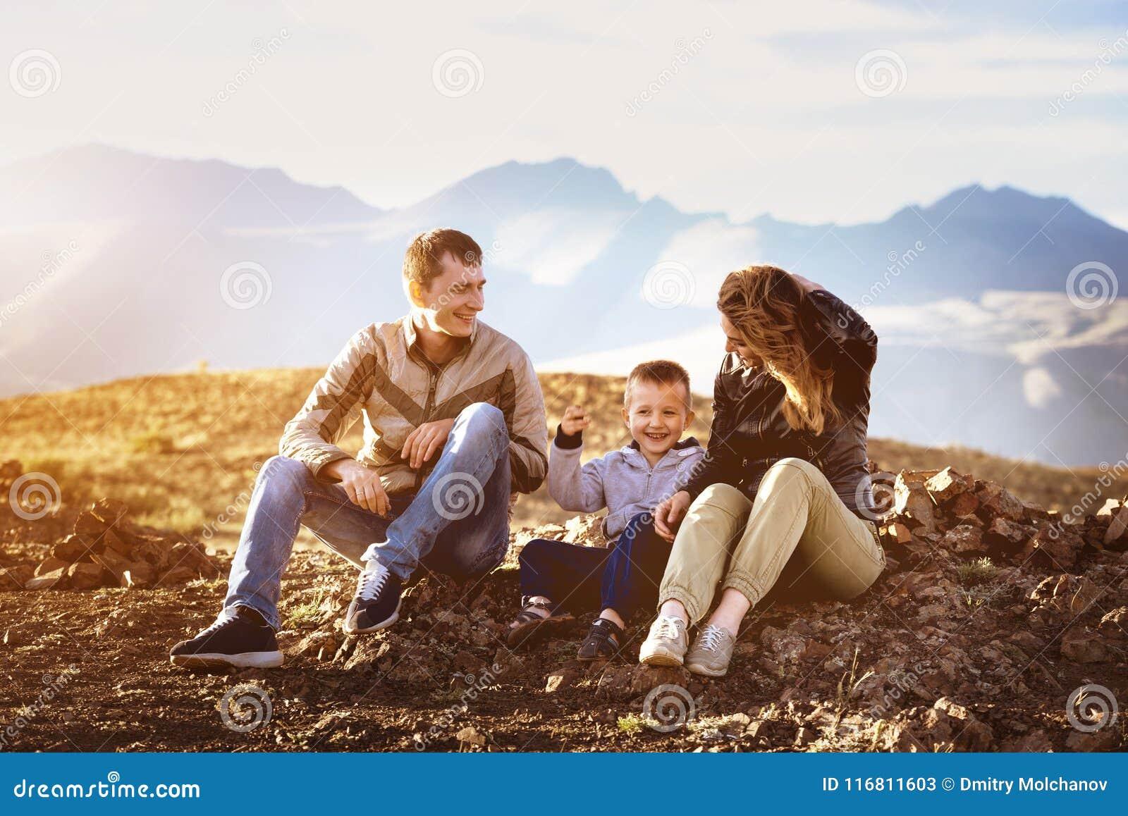 Concetto felice di viaggio di area di montagne di tramonto della famiglia