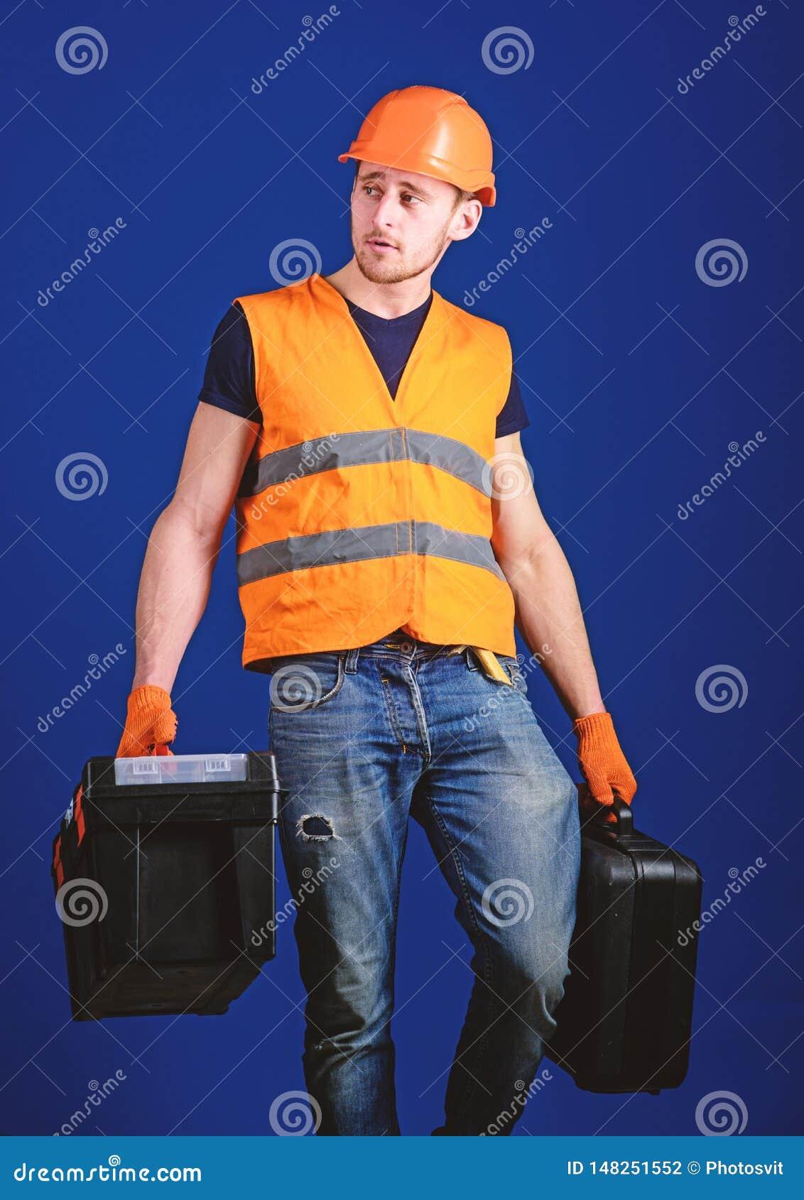 Concetto fornito del riparatore Il lavoratore, tuttofare, riparatore, costruttore sul fronte calmo porta le borse con gli strumen