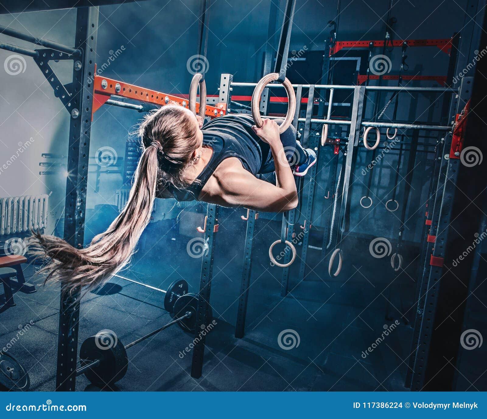 Concetto: potere, forza, stile di vita sano, sport Donna muscolare attraente potente alla palestra di CrossFit