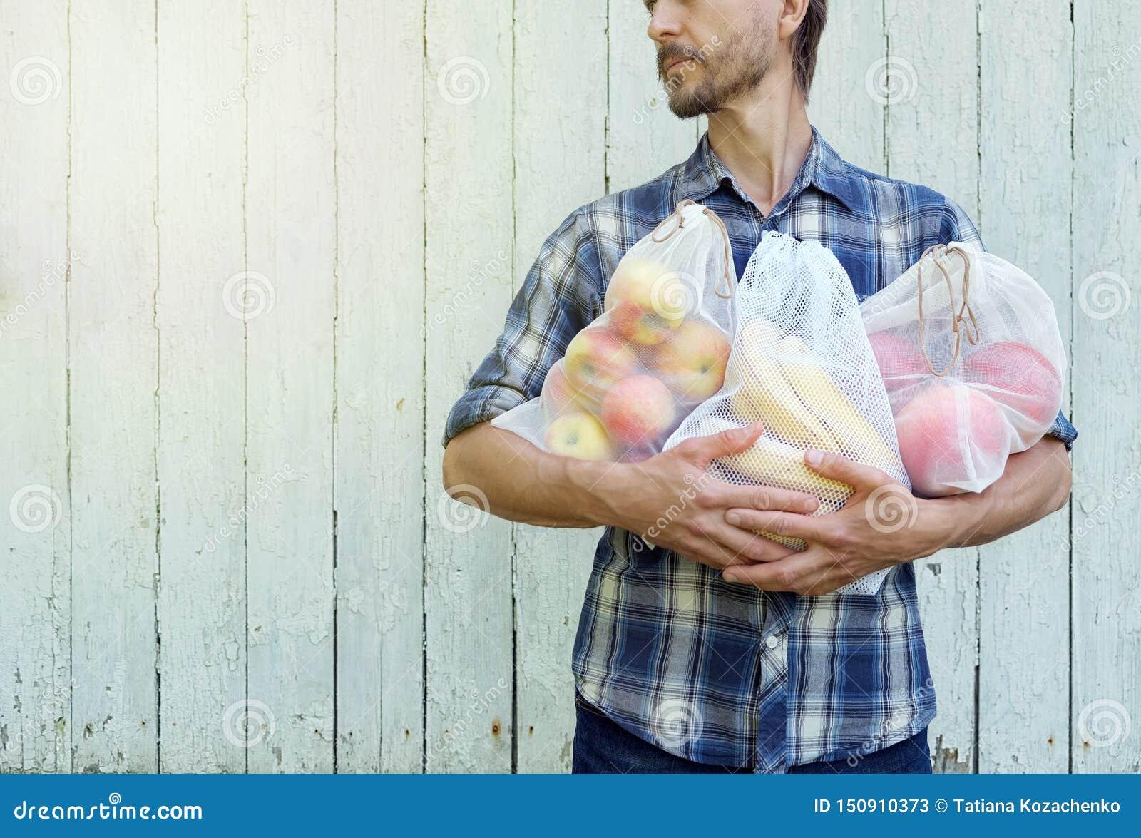 Concetto residuo zero di acquisto Uomo dei pantaloni a vita bassa che tiene le borse riutilizzabili di eco con la frutta fresca P