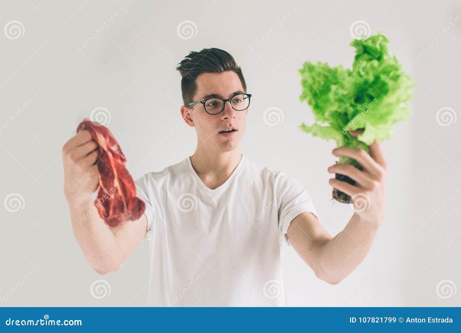 Concetto vegetariano Equipaggi l offerta della scelta delle foglie dell insalata delle verdure o della carne Il nerd sta indossan