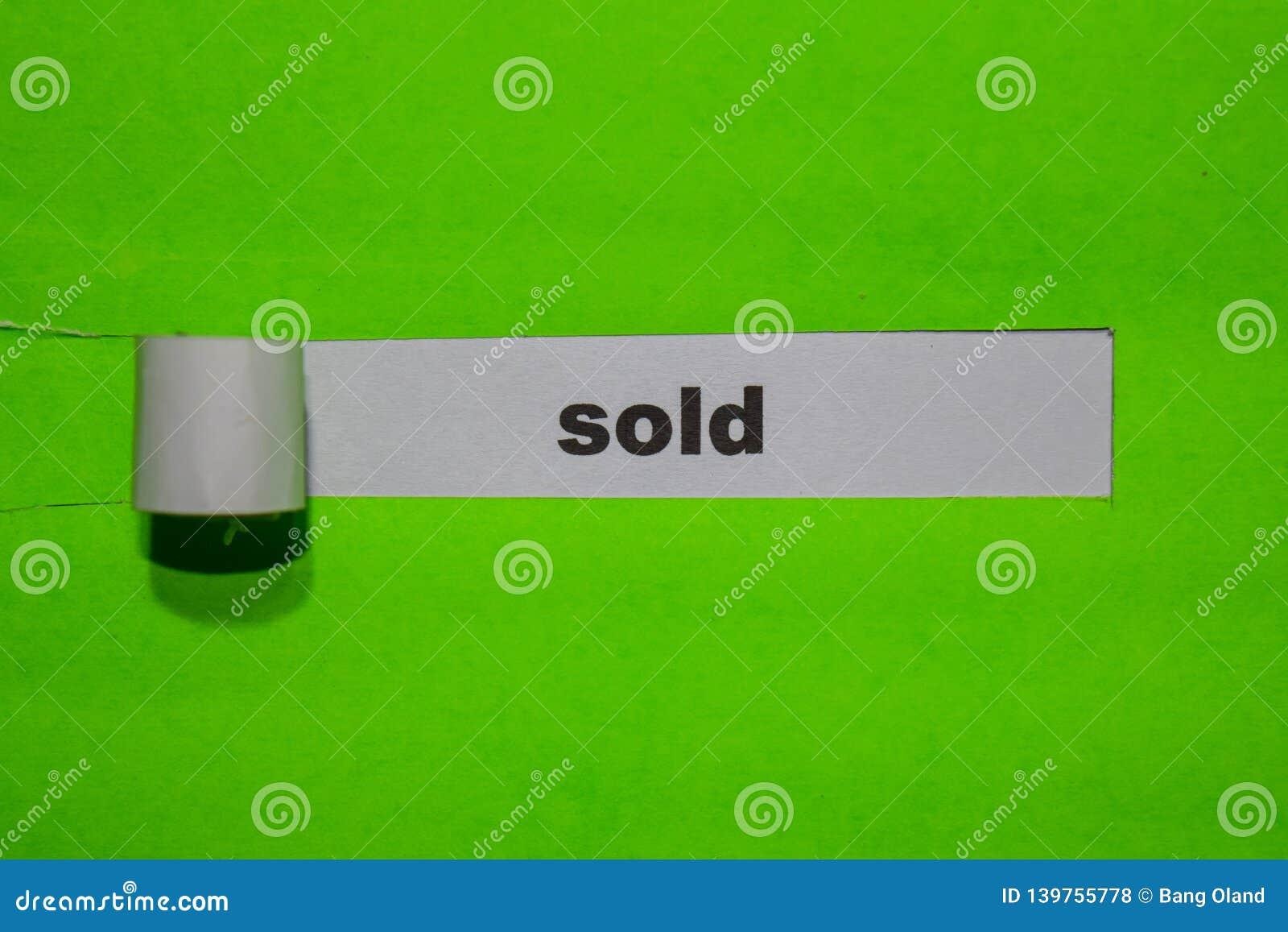Concetto VENDUTA, di ispirazione e di affari su carta lacerata verde