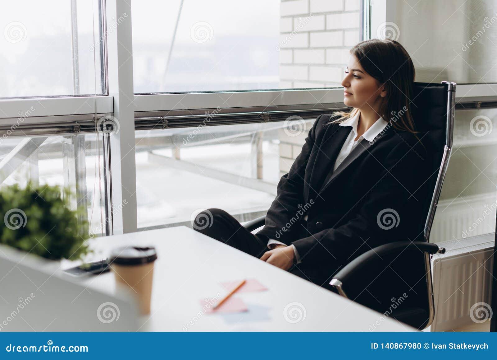 Concezione di successo Ritratto di giovane seduta businesslady splendida nel suo luogo di lavoro nell ufficio