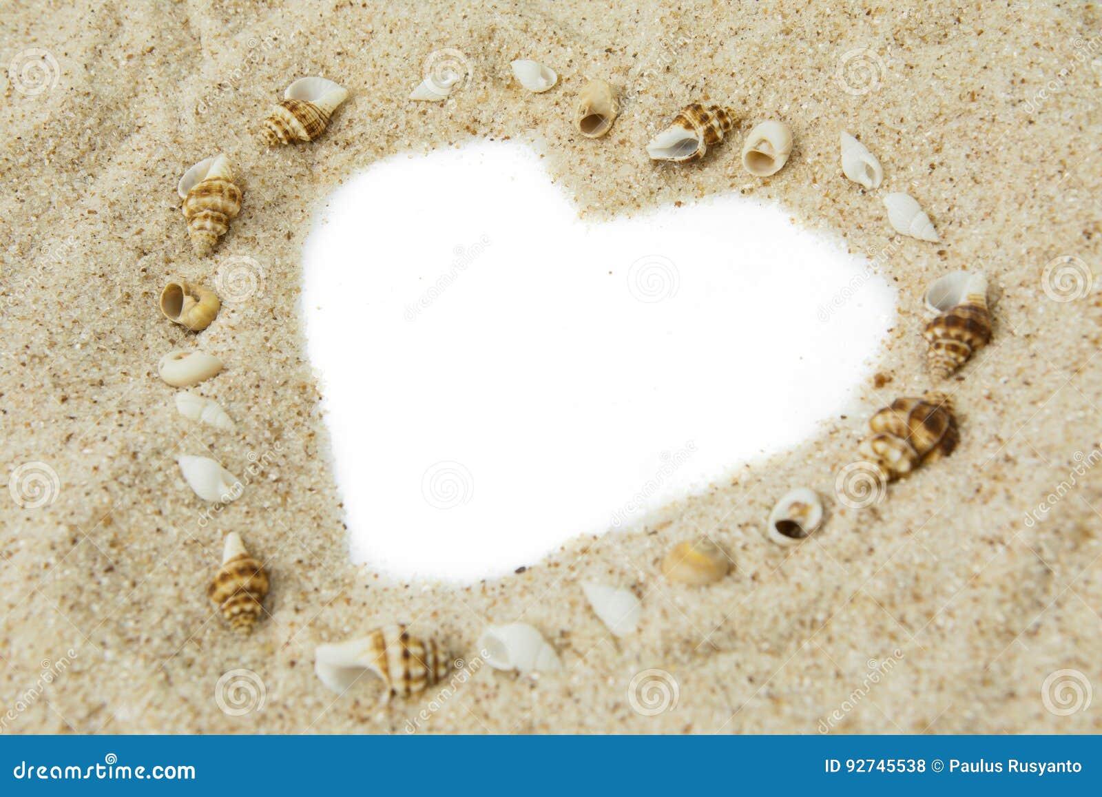 Conchiglie con forma del cuore sulla sabbia
