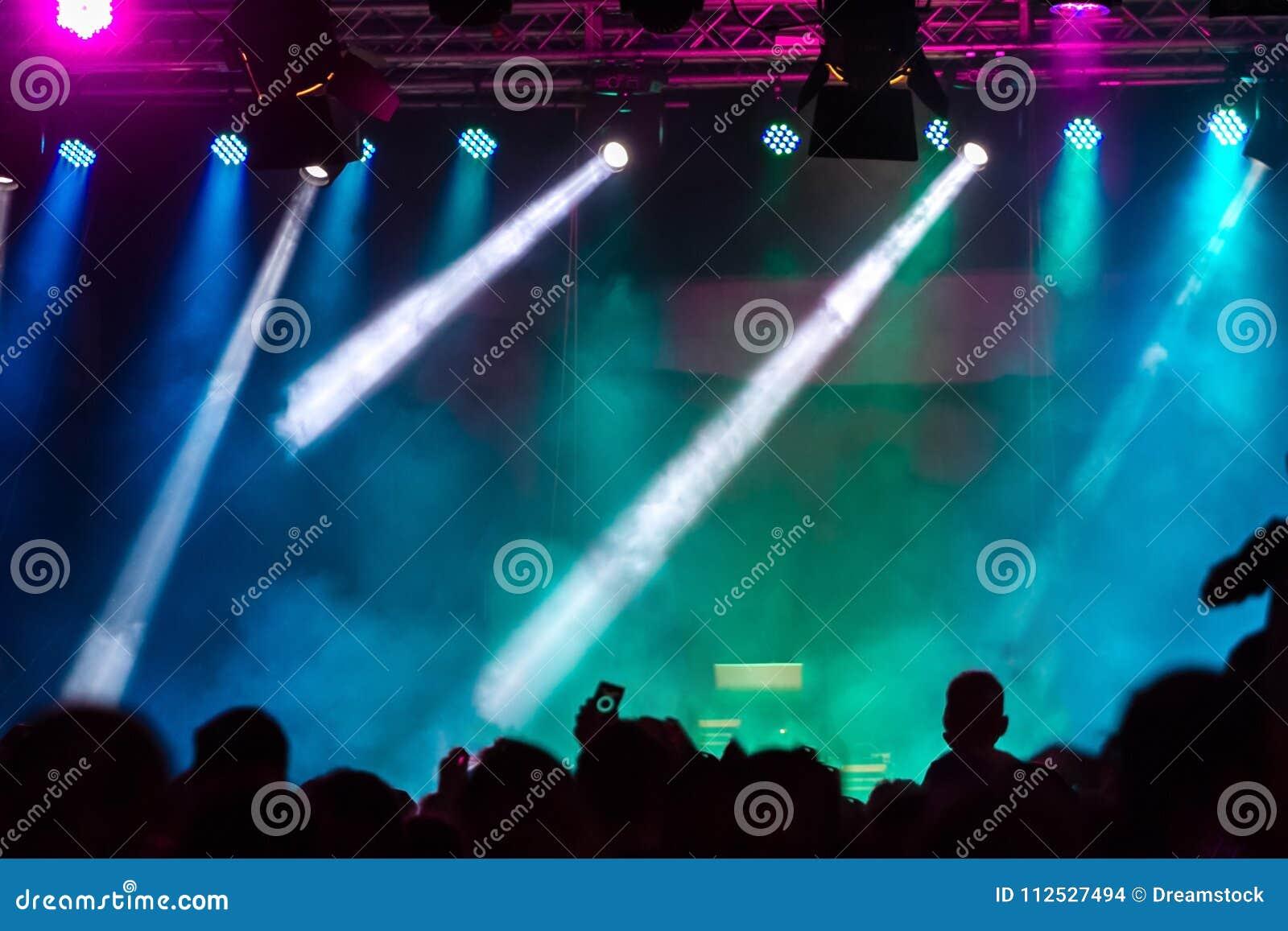 Concierte a la muchedumbre que asiste a un concierto, gente que las siluetas son visibles, retroiluminado por las luces de la eta