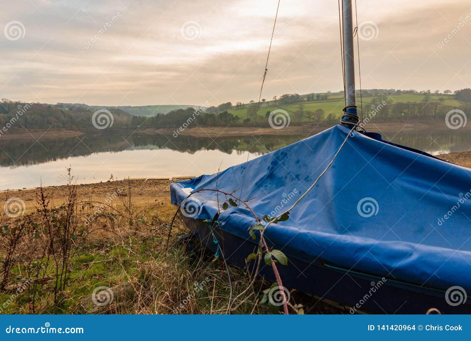 A a conclu des attentes de yacht à sortir sur le réservoir dans le secteur maximal pendant un coucher du soleil de détente